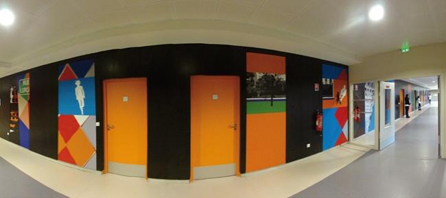 Collège Vauban à Maubeuge : dans le couloir, quinze panneaux monumentaux et dynamiques invitent les étudiants à la mobilité.  Les supports sont pérennes. Les panneaux sont incrustés dans le mur béton noir existant.